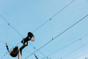 Low Angle View Of Public Address System By Cables Against Clear Blue Sky