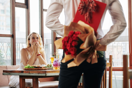 Horizontal shot of unrecognizable young man showing up for date in cafe with rose bouquet and box of chocolate for young woman
