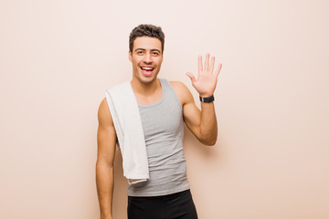 young arabian man smiling happily and cheerfully, waving hand, welcoming and greeting you, or saying goodbye. sport concept