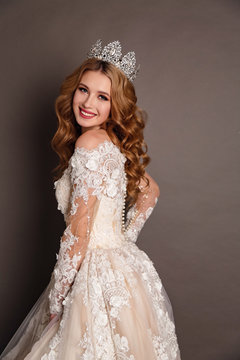 beautiful woman with blond hair in luxurious wedding dress with elegant crown posing in studio