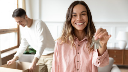 Smiling young wife show keys moving together with spouse