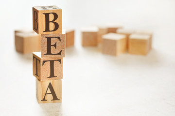 Four wooden cubes arranged in stack with word BETA on them, space for text image at down right corner