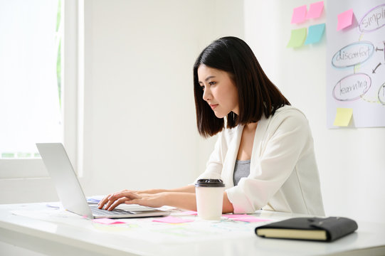 Young asian business woman working on computer laptop in office room with paperwork document on desk