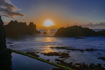 Sunset over the Atlantic ocean horizon, with volcanic rocks formation, long exposure, El Pris, Tacoronte, Tenerife, Canary islands, Spain