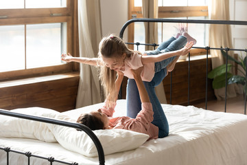 Happy young mom playing with little daughter in bedroom