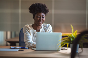 Young black woman in an office smiling to camera, close up. Portrait of young black woman in creative office. Young African American female architect working in an office.