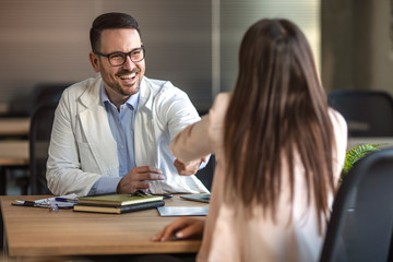 Patient shaking hands to doctor in the office at desk. Woman shaking hands with doctor. Female patient visiting healthcare worker. Male doctor in white coat smiling while shaking hand to female