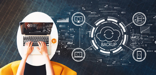 Wall Mural - Backup concept with person using a laptop on a white table