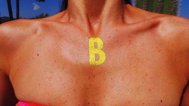 Midsection Of Woman With Letter B On Neck
