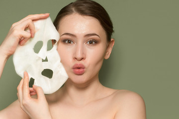 young woman with perfect skin portrait. Face mask near her face. Skin care concept