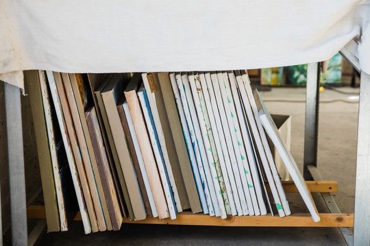 a vertical stack of painted canvases in an artist's loft workspace
