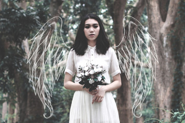 Digital Composite Image Of Woman With Wings Holding Flowers In Forest