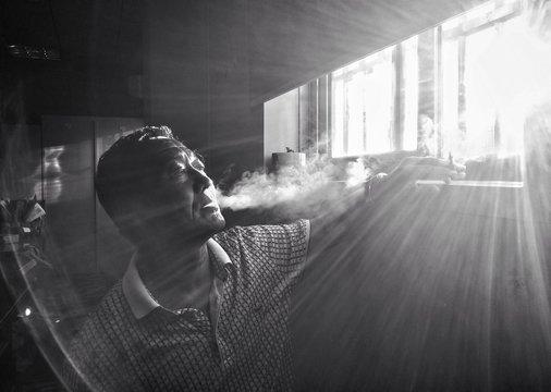 MID ADULT MAN SMOKING INDOORS