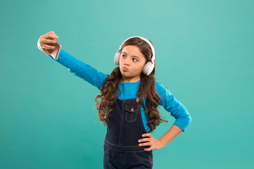 posing for photo. selfie kid in earphones. small child video call on smartphone. small girl hold mobile phone. blogging in modern life. schoolgirl use new technology. live in virtual world
