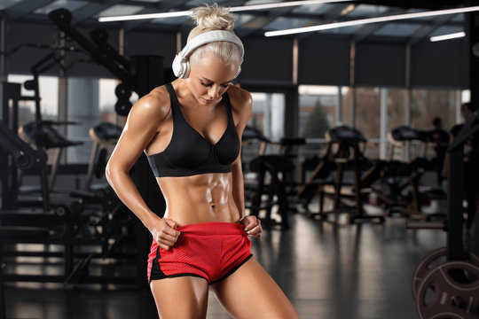 Fitness woman showing abs and flat belly in gym. Beautiful athletic girl, shaped abdominal