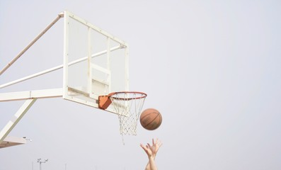Cropped Image Of Hands Throwing On Basketball On Hoop Against Sky