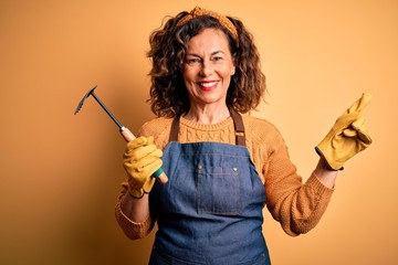 Middle age gardener woman wearing apron holding rake over isolated yellow background very happy pointing with hand and finger to the side