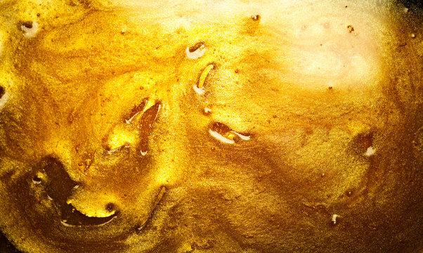 Beautiful abstract golden liquid background, beauty gold backdrop texture. Metallic gold paint, art design. Yellow shimmering surface close-up. Golden bright glitter texture, macro shot