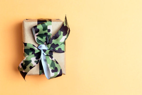 Gift box with khaki ribbon on the yellow background. Defender of the Fatherland Day, February 23.