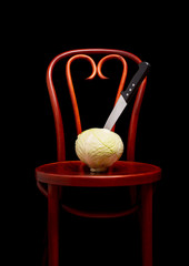 Symbolic conceptual image of a white cabbage on a wooden Thonet chair. A knife is stuck into the vegetable and symbolize cooking, violence, crime, suffering.  On black background.