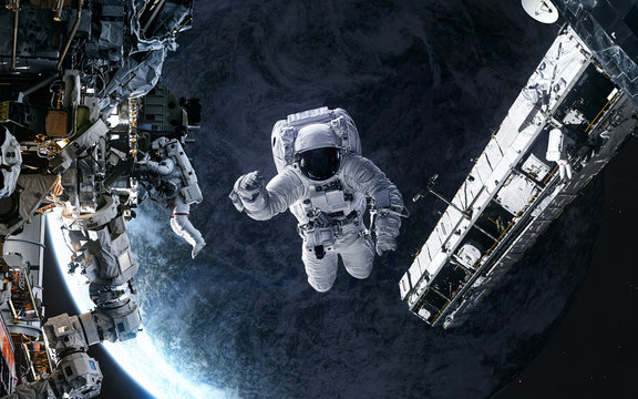 Astronauts, space station in orbit of a deep space planet. Science fiction. Elements of this image furnished by NASA