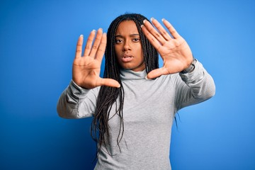 Young african american woman standing wearing casual turtleneck over blue isolated background doing frame using hands palms and fingers, camera perspective