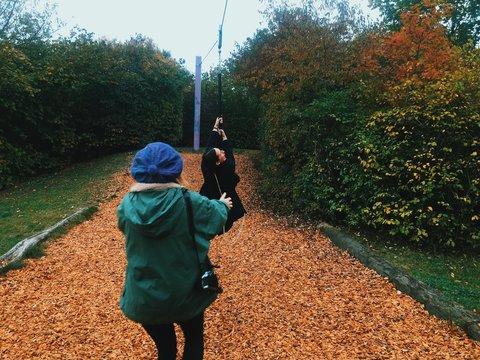 Women Enjoying Zip Line Over Fallen Dry Leaves At Park
