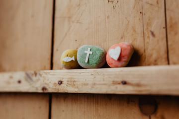 Kommunion, Konfirmation, Firmung, Taufe - bunte Steine mit Kreuz, Fisch und Herz auf Holz