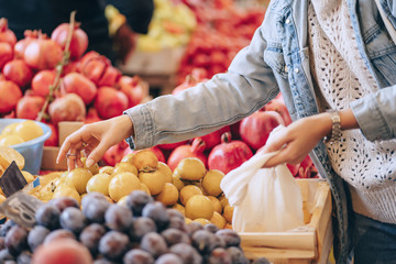Female hands puts fruits and vegetables in cotton produce bag at food market. Reusable eco bag for shopping. Sustainable lifestyle. Eco friendly concept. Wall mural