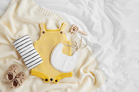 Yellow bodysuit, bib, baby boots and toy on knitted blanket. Set of  kids clothes and accessories  on bed. Fashion newborn. Flat lay, top view