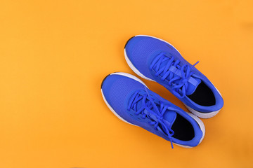 Top view blue running shoes on orange pastel background