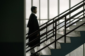 Full Length Serious Man In Graduation Gown Standing On Stairs In Building