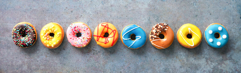 Various colourful donuts in a row on rustical background