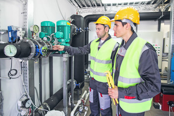 Workers check pipe monometer