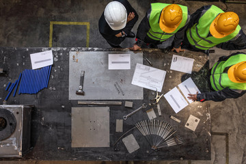 Workers with blueprints at factory