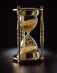 brass hourglass filled with gold