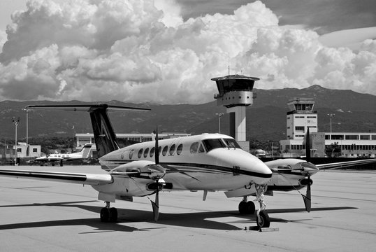 A private turboprop Beechcraft aircraft parked at Ajaccio airport on a black and white shot with stormy clouds and sky during a summer afternoon