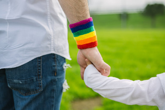 Father with gay pride rainbow flag wristband and his son walking in the park. Paternal concept