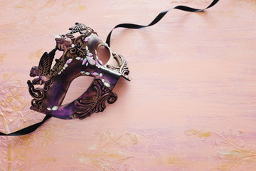 Photo of elegant and delicate purple Venetian mask over pastel wooden background