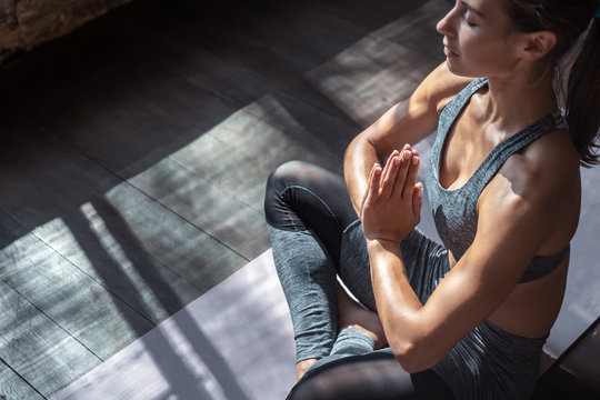 Calm fit sporty healthy mindful woman sit in lotus pose doing yoga exercise breathing fresh air meditating in studio lit with sunlight, stress free peace of mind concept, copy space, close up view