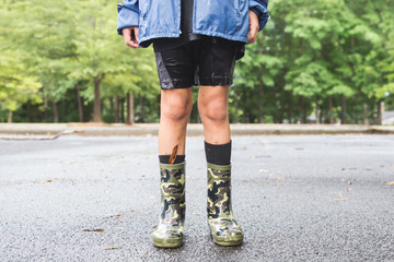 LOW SECTION OF CHILD WEARING BOOTS