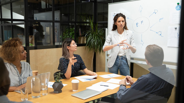 Female speaker hold meeting make board presentation for colleagues