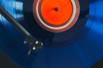 Close up of turntable tonearm playing blue color transparent vinyl record