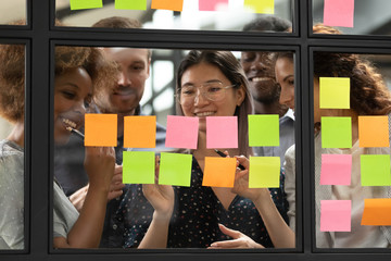 Smiling multiethnic colleagues brainstorm using post it stickers