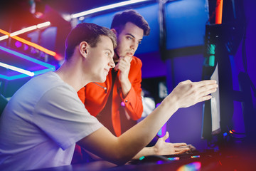 Team of two guys playing online video games analyzes strategy of fighting behind computer monitor in Internet cafe