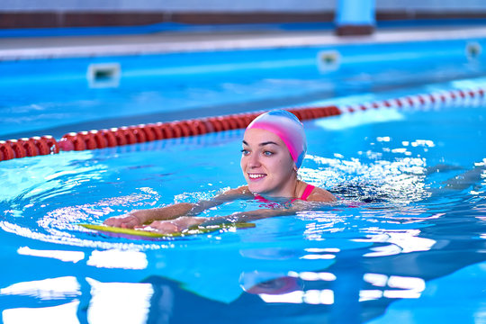 Woman in swimming hat learns to swim in sports pool in leisure center