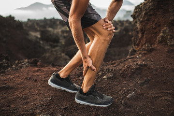 Male runner holding injured calf muscle and suffering with pain. Sprain ligament while running...