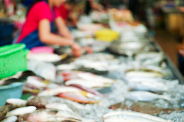 Blurred picture of raw fresh fish on the tray for selling in the market with blurred seller in background