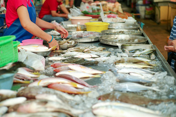 Selective focus on raw fresh fish on the tray for selling in the market with blurred seller in background