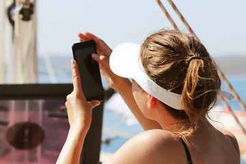A young slender girl in a swimsuit is taking pictures with a mobile phone sitting on the stern of a sailing yacht. A luxury holiday on the water for wealthy people. Prestigious lifestyle. Vacation and